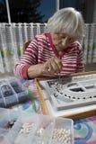 Senior woman making a necklace Stock Photos