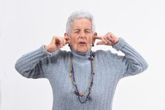 Senior woman making noise hurting her ears on white background.  stock photo