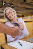Senior woman making payment through NFC technology on mobile phone Stock Image