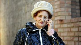 Senior woman making a phone call with her mobile phone outdoor stock video footage