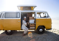 Senior woman making tea in camper van on beach, smiling, portrait (lens flare) Royalty Free Stock Photo