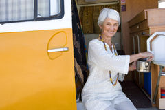 Senior woman making tea in camper van, smiling, portrait Royalty Free Stock Photos