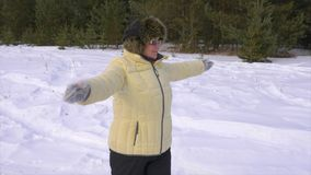 Senior woman making warming up exercises. Senior woman in sunglasses making warming up exercises. Happy sporty woman in winter forest stock video footage
