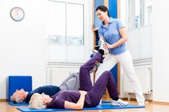 Senior woman and man doing assisted floor exercises with physiot Stock Images