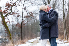 Senior woman and man embracing each other in winter Stock Photos