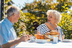 Senior woman and man having breakfast sitting in their garden ou Royalty Free Stock Image