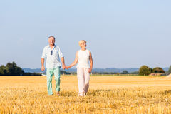 Senior woman and man holding hands having walk Stock Image