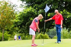 Senior woman and man playing golf putting on green Royalty Free Stock Image