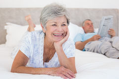 Senior woman with man reading newspaper on bed Stock Photo