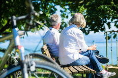 Senior woman and man at rest on bike trip. Senior women and men at rest on bike trip sitting on a bench stock image