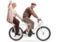 Senior woman and man riding a tandem bycicle and waving royalty free stock images