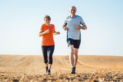 Senior woman and man running or jogging on a field stock photos