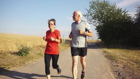 Senior woman and man running or jogging on a field stock video footage