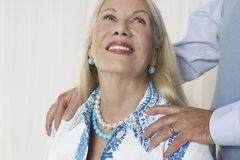 Senior Woman With Man's Hands On Shoulders Royalty Free Stock Photos