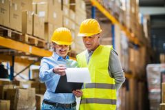Senior woman manager and man worker working in a warehouse. Senior woman manager with clipboard and a man worker working together in a warehouse Royalty Free Stock Photography