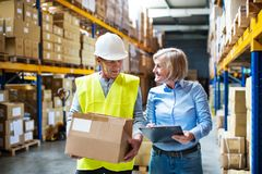 Senior woman manager and man worker working in a warehouse. Senior woman manager and a man worker working together in a warehouse Stock Image
