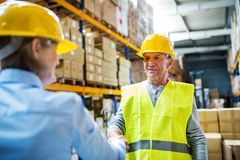 Senior woman manager and man worker working in a warehouse. Senior woman manager and a man worker working together in a warehouse, shaking hands Stock Photo