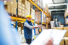 Senior woman manager and man worker working in a warehouse. Unrecognizable senior woman manager and a man worker working together in a warehouse Royalty Free Stock Photo