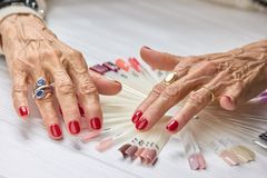 Senior woman manicured hands. Old woman nails covered with perfect red polish, nails samples collection Royalty Free Stock Images