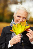 Senior woman with maple leaves Stock Photo