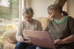 Senior woman and mature woman using a laptop stock photos