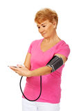 Senior woman measuring blood pressure with automatic manometer Royalty Free Stock Images