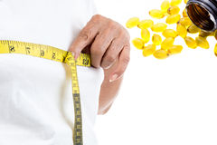 Senior woman measuring her waist with fish oil Stock Image
