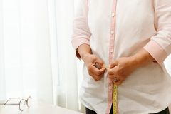Senior woman measuring her waist by measuring tape stock photography