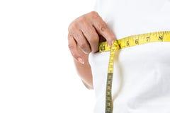 Senior woman measuring her waist on white. Royalty Free Stock Photo