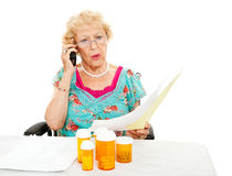 Senior Woman - Medical Expenses. Disabled senior woman shocked by the cost of medical care and prescription medicine.  White background Royalty Free Stock Photo