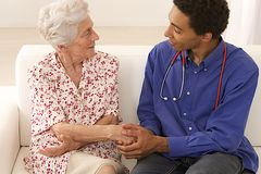 Senior woman medical visit at home. Doctor or care giver holding elderly lady's hands Stock Photos