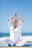 Senior woman meditating beach Royalty Free Stock Photos