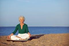 Senior woman meditating on beautiful beach Royalty Free Stock Images