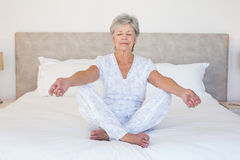 Senior woman meditating in bed Royalty Free Stock Photography