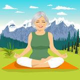 Senior woman meditating and exercising yoga lotus position in mountains Royalty Free Stock Image