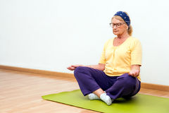 Senior woman meditating in gym. Royalty Free Stock Photography