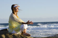 Senior woman meditating at ocean Royalty Free Stock Images