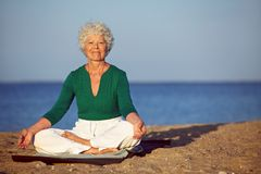 Senior woman meditating on sandy beach Royalty Free Stock Photos