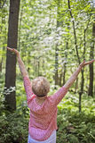 Senior woman meditation/praise. A back view of a senior woman standing in a forest a meditation/praise pose stock photos