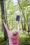 Senior woman meditation/praise. A back view of a senior woman standing in a forest a meditation/praise pose holding up bible stock image