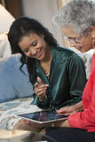 Senior woman meeting with agent. Mature Black women sharing a digital tablet at a home meeting with her agent Royalty Free Stock Image