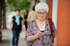 Senior Woman Messaging On Smartphone Stock Photos