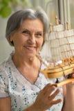 Senior woman with miniature ship Royalty Free Stock Image