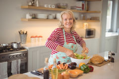 Senior woman mixing vegetables salad in kitchen Royalty Free Stock Photography
