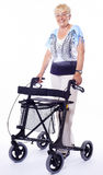 Senior woman with modern walker. Smiling senior woman with happy expression in face with a modern walker for handicapped People. Image taken isolated on white Royalty Free Stock Photos