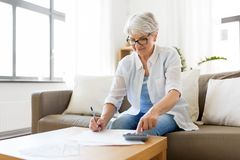 Senior woman with money and bills at home. Finances, savings, annuity insurance and people concept - senior woman with calculator and bills counting dollar money stock image