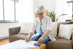 Senior woman with money and bills at home. Finances, savings, annuity insurance and people concept - senior woman with calculator and bills counting dollar money royalty free stock photos