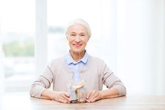 Senior woman with money in glass jar at home Royalty Free Stock Photography