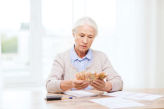 Senior woman with money and papers at home stock photo
