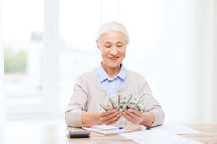Senior woman with money and papers at home Royalty Free Stock Photo